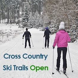 Three people ski on snow-covered trails. Text: Cross Country Ski Trails Open