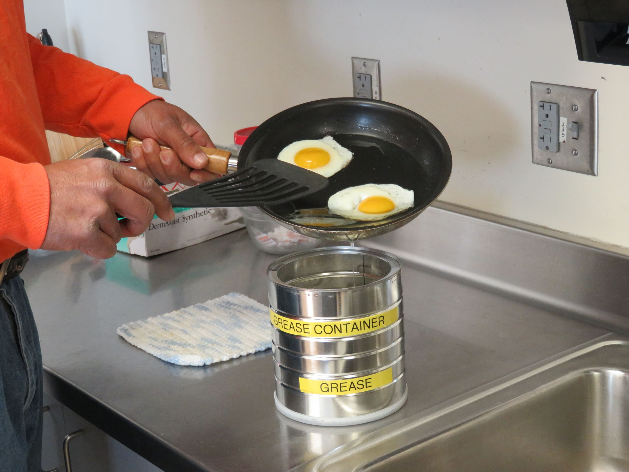 Person putting grease from frying eggs into a coffee can-sized collection container.