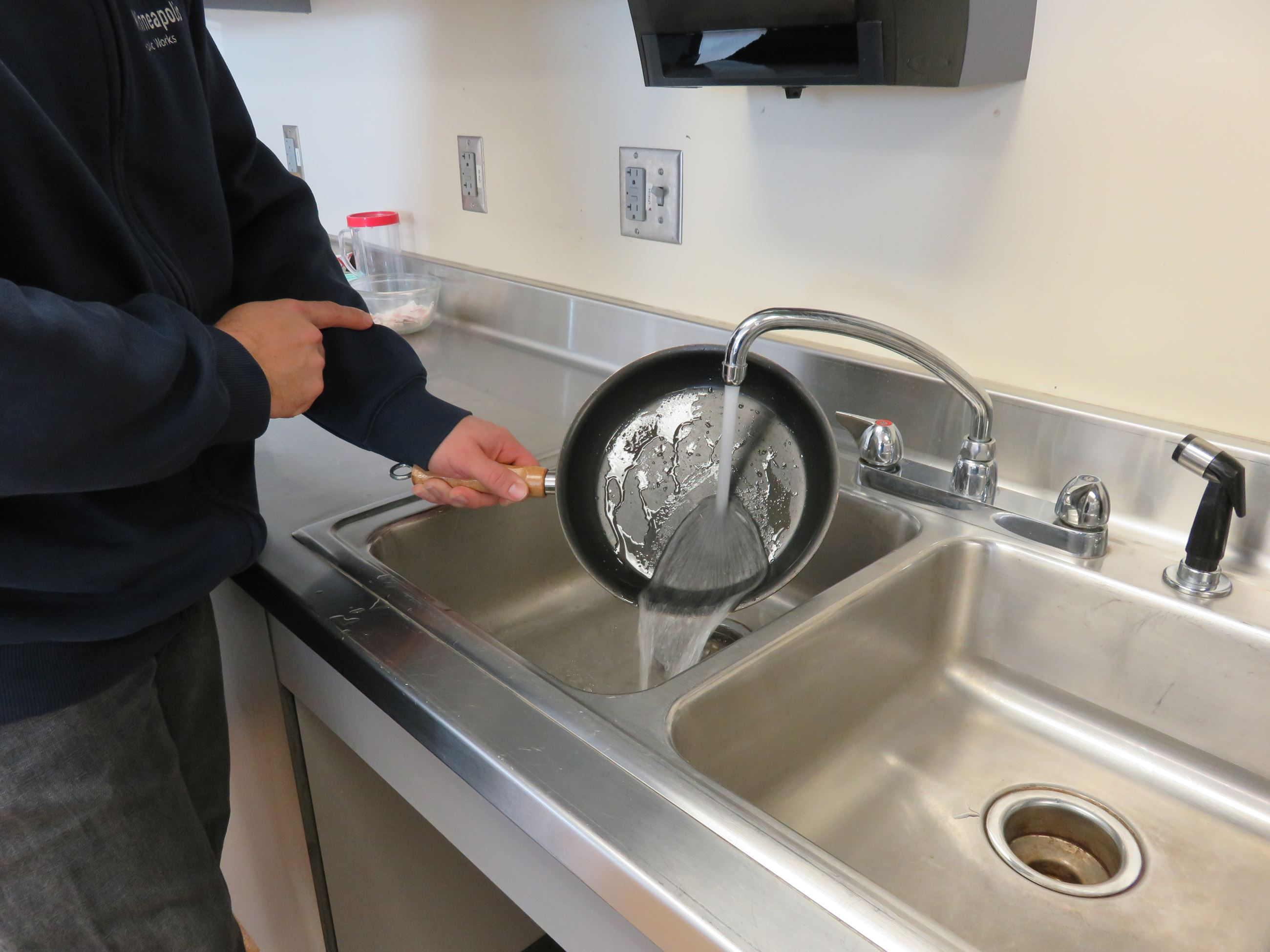 Person rinsing small fry pan with water.