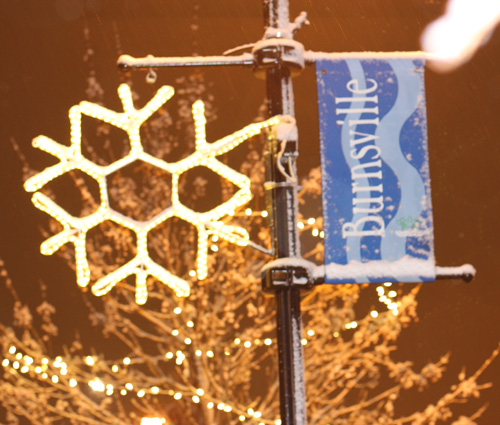 Burnsville Flag in the Snow Next to Lighted Snowflake on Post